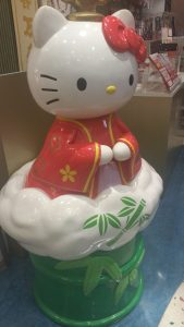 Kawaii Hello Kitty statue in red robe sitting on bamboo