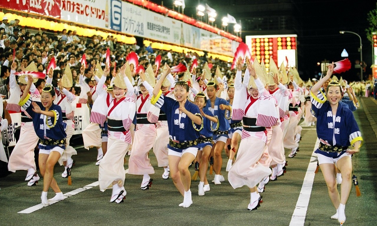 Dancers in traditional costume including straw hats parade at the Awa Dance Festival. This dance is popular at many Japanese summer festivals.