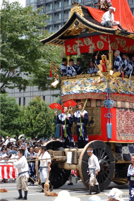 Priests ride a massive portable shrine on wheels in a parade for the Gion Festival in Kyoto. This is a popular Japanese summer matsuri festival.
