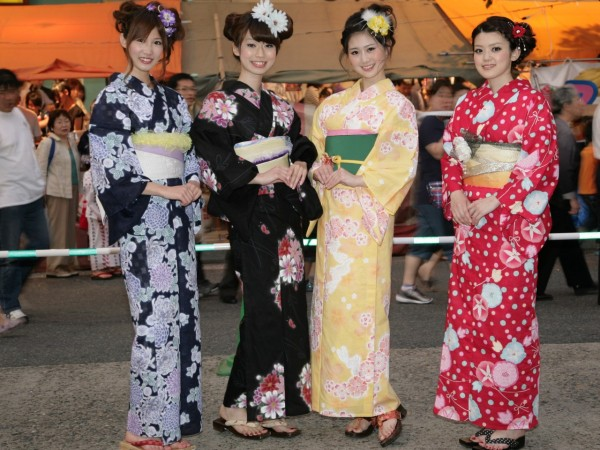 Four Japanese girls wearing colourful traditional yukata robes like a summer cotton version of a kimono at a summer matsuri festival