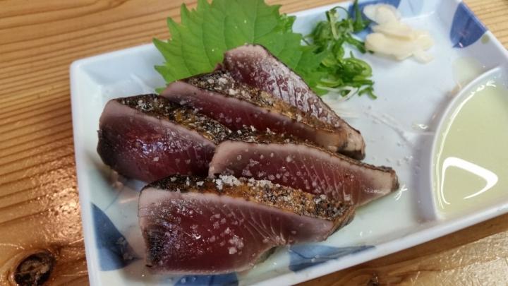 Katsuo no tataki is a Kochi local food and is bonito tuna seared black on the outside over straw fire